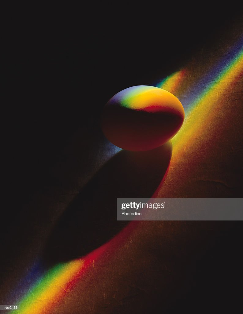 an egg lies on a dark surface as a color spectrum runs over it : Foto de stock
