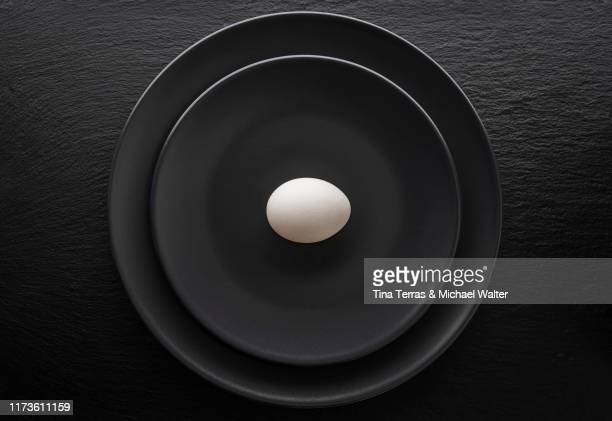 an egg on a black plate. the plate is standing on a black slate plate. - single object stock pictures, royalty-free photos & images