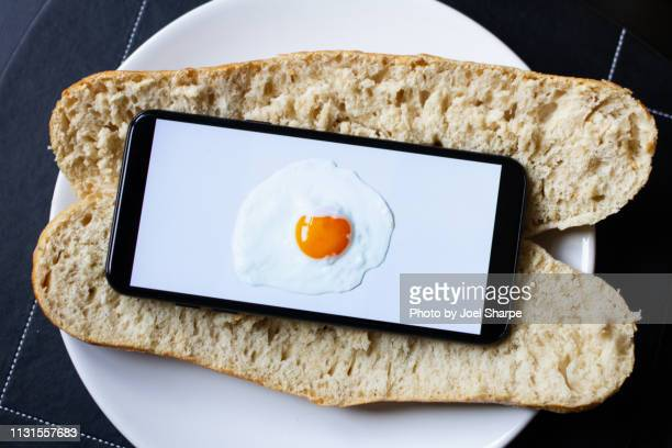 an egg on a phone on a baguette - verslaving stockfoto's en -beelden