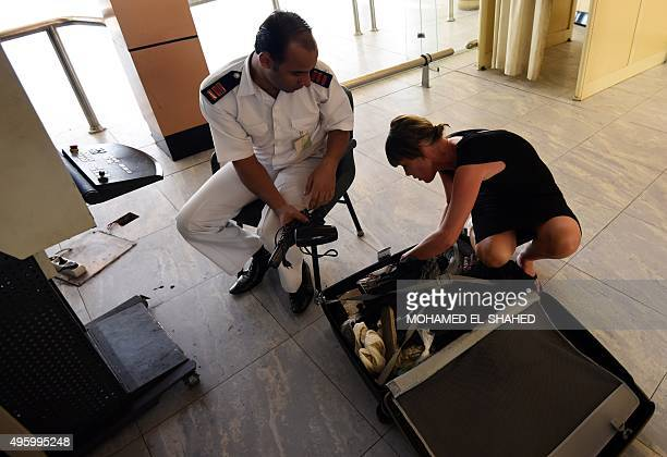 An Egyptian airport security guard checks the contents of a British tourist's suitcase at the airport in Egypt's Red Sea resort of Sharm ElSheikh on...
