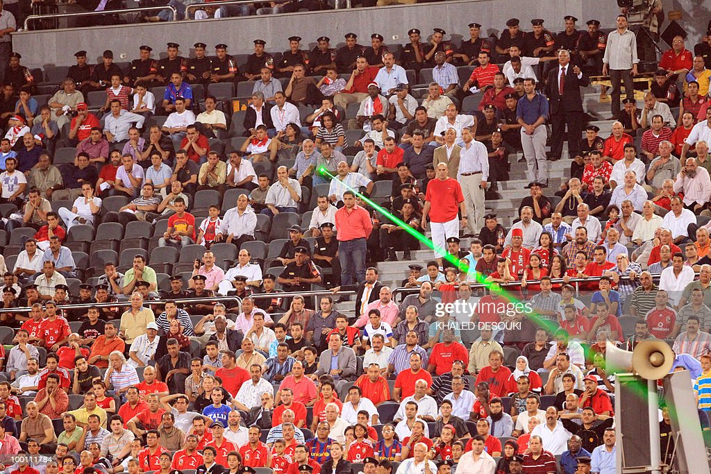 An Egyptian Al-Ahly's fan directs a lase