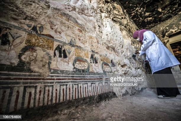 An Egyptian archaeologist brushes the painted walls of Tomb TT28 which originally dated to the Middle Kingdom but was reused the Late period which...