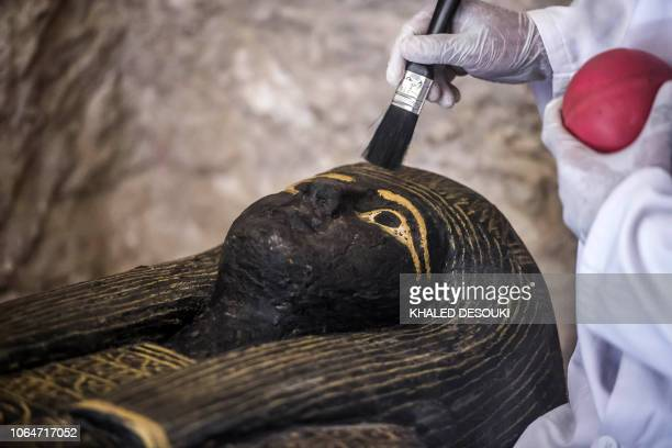 An Egyptian archaeologist brushes the top of a carved black wooden sarcophagus inlaid with gilded sheets dating to Egypt's Late period discovered by...