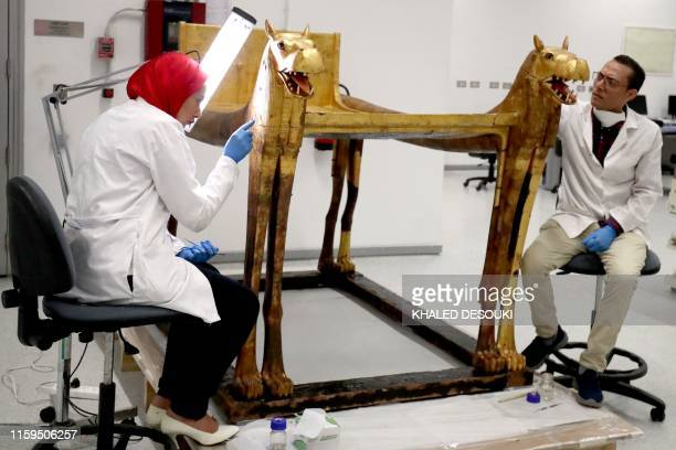 An Egyptian archaeologist restores a piece of King Tutankhamun's collection at the conservation center in the Grand Egyptian Museum in Cairo on...