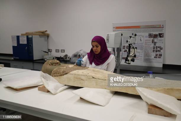 An Egyptian archaeologist restores the coffin of King Tutankhamun at the conservation center in the Grand Egyptian Museum on August 4 2019 For the...