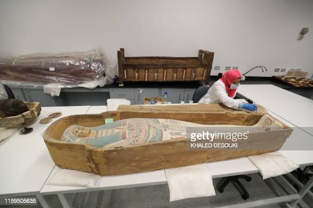 An Egyptian archaeologist restores the coffin of King Tutankhamun at the conservation center in the Grand Egyptian Museum on August 4, 2019. - For...