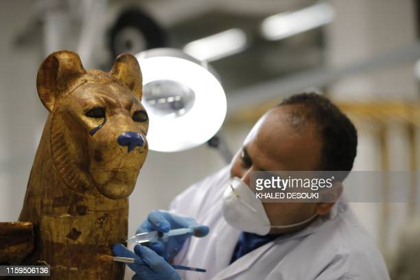 An Egyptian archaeologist restores the throne of the throne of King Tutankhamun at the conservation center in the Grand Egyptian Museum on August 4...