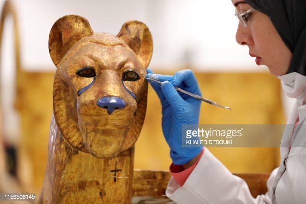An Egyptian archaeologist restores the throne of the throne of King Tutankhamun at the conservation center in the Grand Egyptian Museum on August 4,...