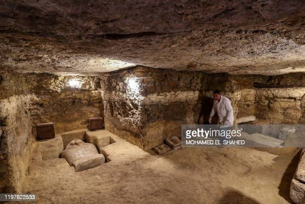 An Egyptian archeologist inspects a burrial chamber among many 3000yearold communal tombs dedicated to high priests discovered in AlGhoreifa in Tuna...