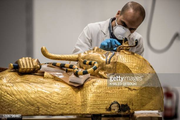 An Egyptian archeologist, wearing personal protective equipment, performs restorations on the golden sarcophagus of the ancient Egyptian Pharaoh...
