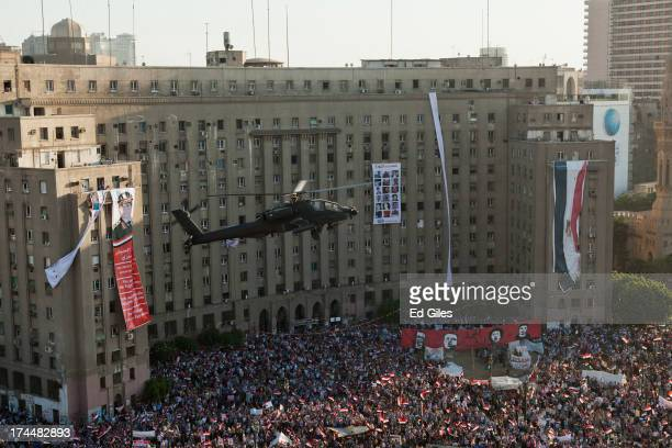 An Egyptian Army Apache helicopter flies over a crowd of promilitary demonstrators at Tahrir Square on July 26 2013 in Cairo Egypt Protesters...