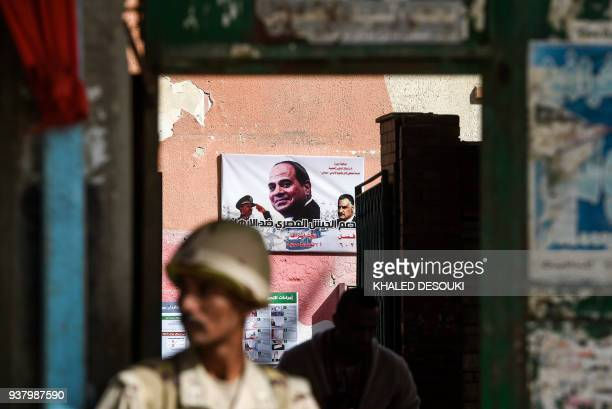 An Egyptian army conscript stands guard outside a polling station before the start of the first day of the 2018 presidential elections in Boulaq...