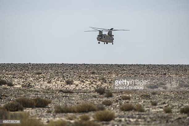 An Egyptian army helicopter flies over the crash site of an A321 Russian airliner in Wadi alZolomat a mountainous area in Egypt's Sinai Peninsula on...