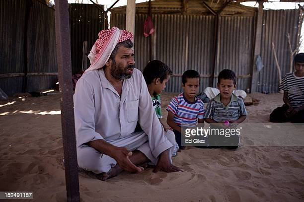 An Egyptian bedouin man sits with his three sons in the village of Al Muqattah in Egypt's restive North Sinai region September 20 2012 The village of...