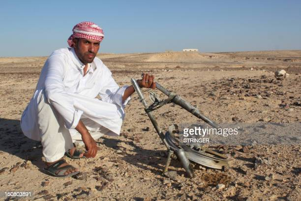 An Egyptian Bedouin shows the pieces of metal at the scene of an explosion on August 26 2012 in the Sinai Peninsula near the Israeli border where a...
