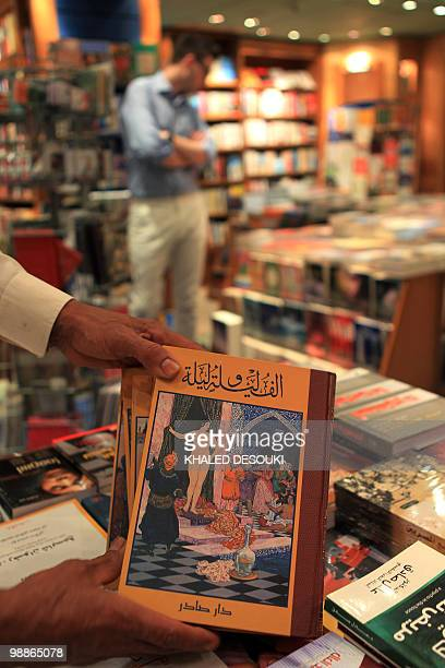 An Egyptian book vendor holds copies of 'One Thousand and One Nights' known in English as 'Arabian Nights' at a bookstore in Cairo on May 5 2010 The...