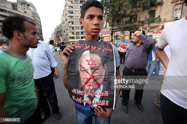 An Egyptian boy holds a crossedout portrait of presidential candidate Ahmed Shafiq decorated with a Star of David as he protests in Cairo's Tahrir...