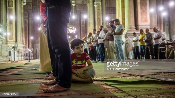 An Egyptian boy sits near his father taking part in the Tarawih recitations on the occasion of Laylat alQadr which falls on the 27th day of the...
