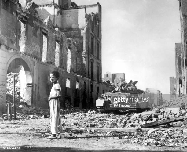 An Egyptian boy surveys the devastation as a British tank moves through a ruined street in Port Said now occupied by AngloFrench troops awaiting the...