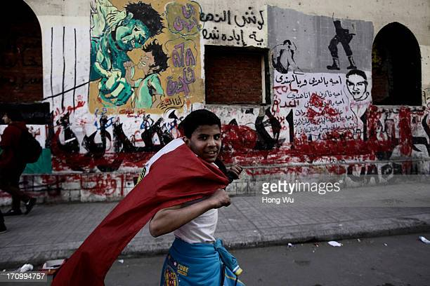 An Egyptian child carries a national flag during clashes with riot police in Tahrir Square on March 03 2013 in Cairo Egypt After two years since the...