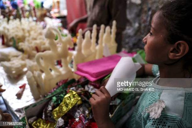 An Egyptian child gazes at statuettes made from sugar in front of a candy factory in the capital Cairo on November 2 ahead of celebrations of the...