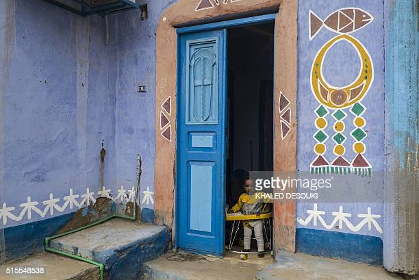 TOPSHOT An Egyptian child looks out from the doorway of his family's home in Gharb Aswan village near Aswan 900 kilometres south of the capital Cairo...
