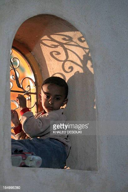 An Egyptian Christian Coptic boy sits in the bay of a window as he watches people gathering at the final resting place of Coptic Pope Shenuda III the...