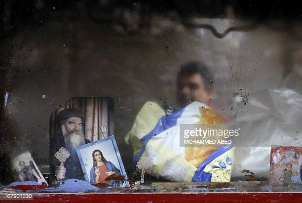 An Egyptian Christian vendor is reflected on a glass decorated with an icon of Jesus Christ and a picture of Coptic Pope Shenouda III of Alexandria...