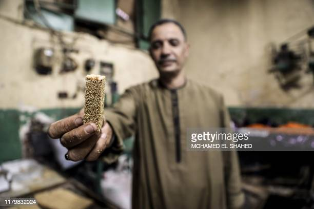 An Egyptian confectioner shows a sweet sesame bar at a candy factory in the capital Cairo on November 2 ahead of celebrations of the Muslim Prophet...