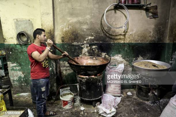 An Egyptian confectioner stirs a large pot of melted sugar at a candy factory in the capital Cairo on November 2 ahead of celebrations of the Muslim...