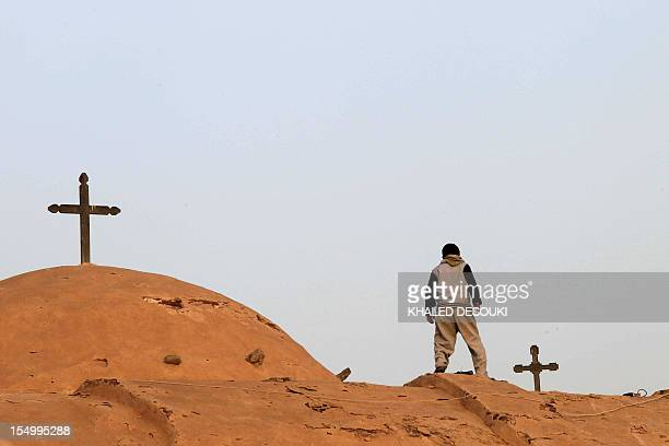An Egyptian Coptic boy looks down from the roof of the Bishoy Monastery in Beheira province 150 kms northwest of Cairo on March 20 the final resting...