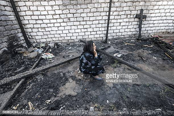 An Egyptian Coptic Christian woman sits on July 24 in the rubble of a makeshift chapel that was torched a few months ago during clashes in the...