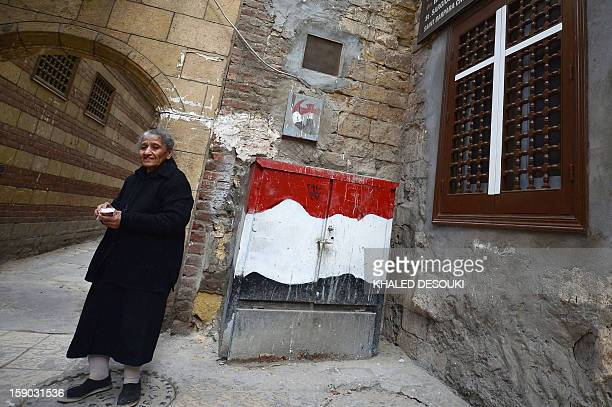 An Egyptian Coptic Christian woman stands outside a church on January 6 2013 in the historical center of Cairo The Copts of Egypt will celebrate on...