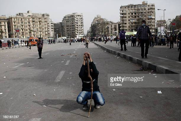 An Egyptian demonstrator squats down during a lull in fighting between protesters and riot police during a demonstration in Tahrir Square on January...