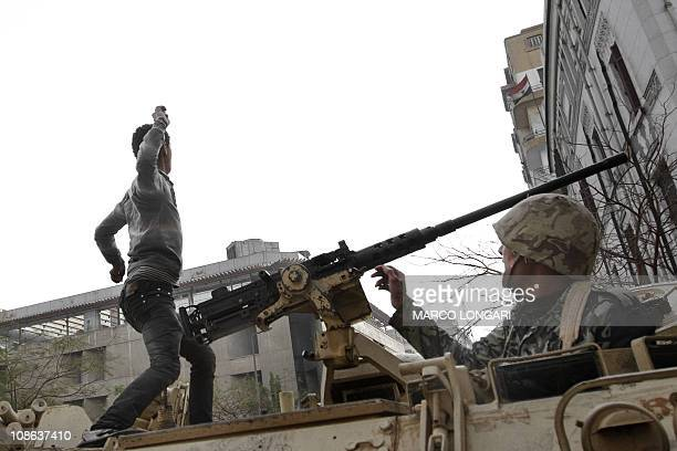 An Egyptian demonstrator throws a stone from atop an army APC as police opened on crowds near a central square in downtown Cairo on January 29 2011...