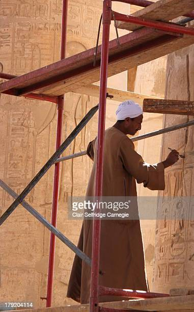 CONTENT] An Egyptian dressed in traditional robes works at restoring a column decorated in Egyptian hieroglyphs cartouches and gods at the Ramesseum...