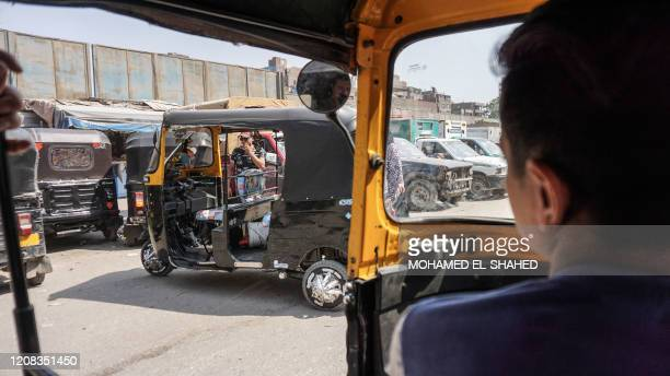 """An Egyptian driver arrives in his rickshaw, also known as """"tuk-tuk"""", to a taxi stop to wait for passengers in the capital Cairo, on September 16,..."""