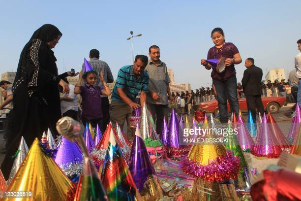 An Egyptian family buy colourful party hats for their daughters following morning prays celebrating the start of the threeday feast known in Arabic...