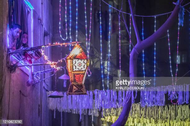 An Egyptian family watch from their window as youths decorate their residential street in preparation for the Muslim holy month of Ramadan in Cairo's...