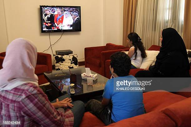 An Egyptian family watches the royal wedding of Prince William and Kate Middleton on a TV screen in Cairo on April 29 2011 AFP PHOTO/KHALED DESOUKI