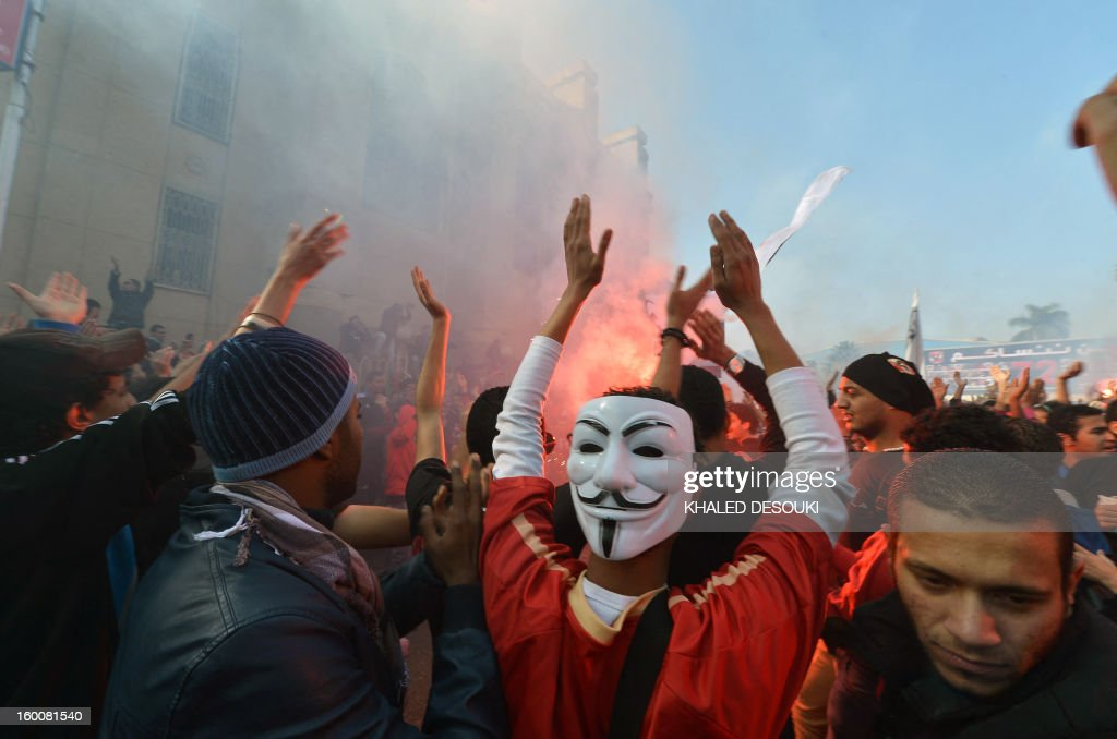 An Egyptian fan of Al-Ahly football club wearing a Guy Fawkes mask used by the Anonymous movement celebrates with other club supporters outside its headquarters in Cairo on January 26, 2013 after a court sentenced 21 people to death over a football riot that killed more than 70 people last year. The clashes in Port Said in February last year between fans of home side Al-Masry and Cairo's Al-Ahly had left more than 70 people dead and sparked days of violent protests in Cairo, in which another 16 people were killed.