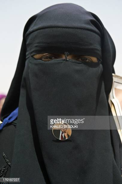 An Egyptian female supporter of Egypt's former president Hosni Mubarak wears a badge bearing the portrait of the fallen dictator on her niqab outside...