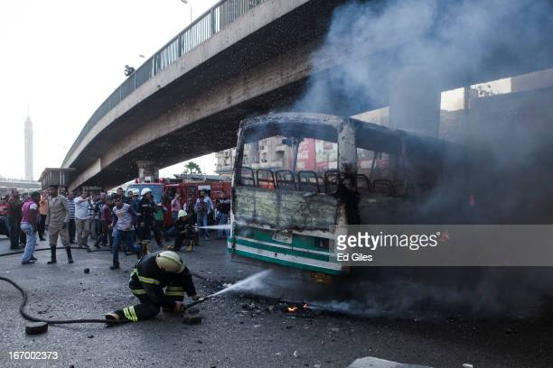 An Egyptian firefighter extinguishes a burning bus set alight during violent clashes between supporters of Egyptian President Mohammed Morsi and...