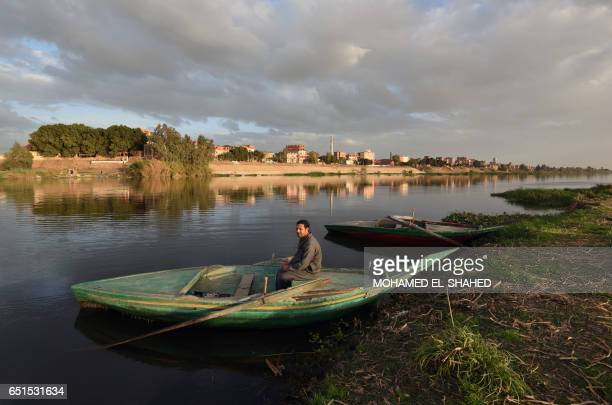 An Egyptian fisherman sits in his boat in the Egyptian Nile Delta province of alMinufiyah near the town of Ashmun on March 10 2017 / AFP PHOTO /...