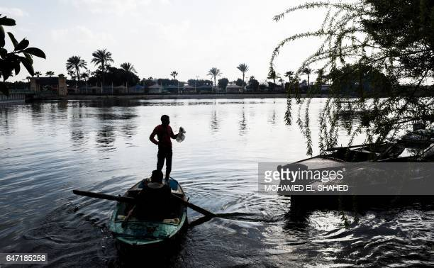 An Egyptian fisherman stands in his boat by the Nile riverbanks off the southern district of Maadi in the Egyptian capital Cairo / AFP PHOTO /...