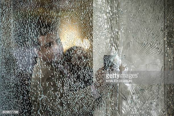 TOPSHOT An Egyptian forensic expert inspects a bullet riddle window at the entrance of the Three Pyramids hotel in Cairo's alHarm district on January...