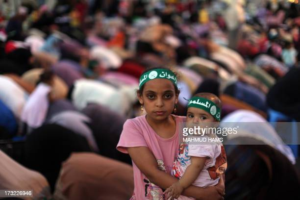 An Egyptian girl holds a baby as Egyptian supporters of the Muslim Brotherhood and Egypt's ousted president Mohamed Morsi pray outside Cairo's Rabaa...