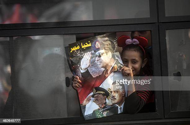 An Egyptian girl looks out from a public bus as she holds a poster with a portrait of late president Gamal Abdel Nasser Anwar Sadat and Egypt's...