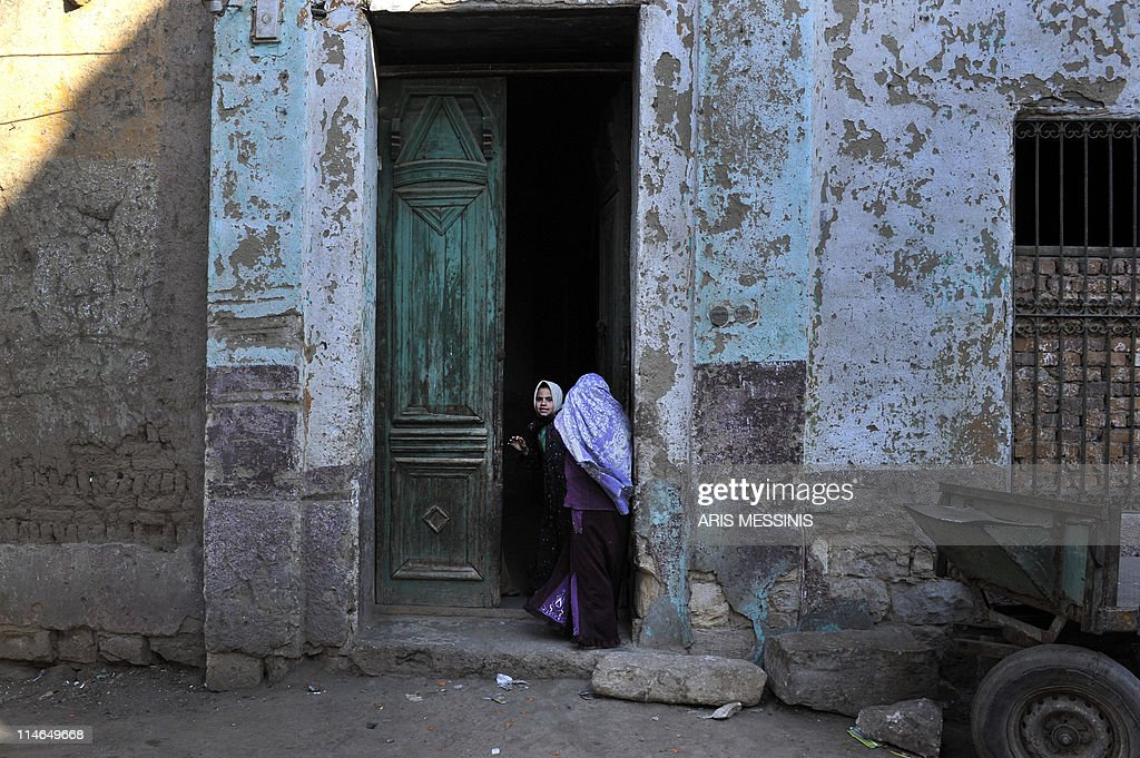 An Egyptian girl stands next to a woman at the entrance of a house in the village of Sol in the province of Helwan, some 100 kms south of Cairo, on March 13, 2011 as construction began on a church that was set ablaze last week in the village, sparking deadly clashes between Muslims and Christians.