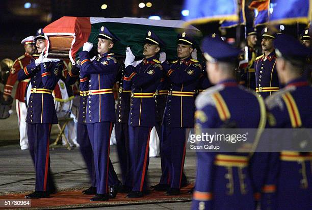 An Egyptian honour guard carries the casket bearing the remains of Palestinian leader Yasser Arafat November 11 2004 at Cairo International Airport...